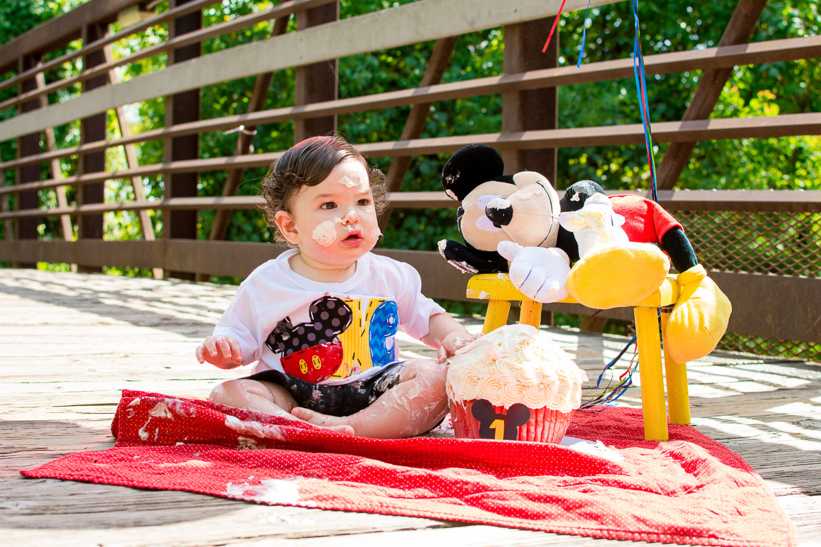 An outdoor first birthday cake smash photography session in Sugarland, Texas with Mickey Mouse by Kristen Richards Photography