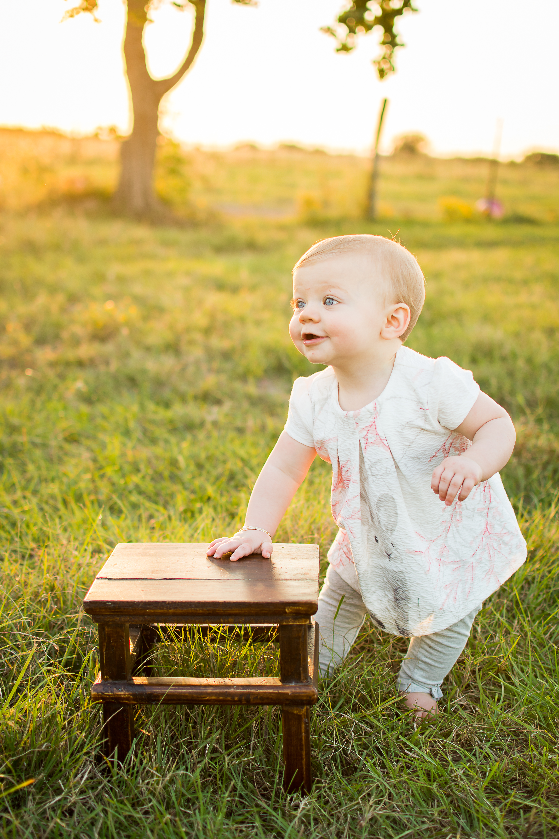 Photograph of a toddler girl with blue eyes in a grass field by Sealy, Texas family photographer Kristen Richards